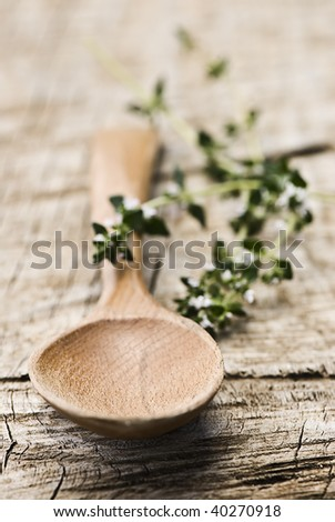 Rustic wooden spoon with fresh herbs on an old wooden board