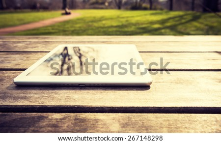 Rustic wooden table with digital tablet and trees reflecting on black screen. View from above with copy space