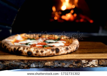 Rustic wooden table with pizza Margarita with fire in the back