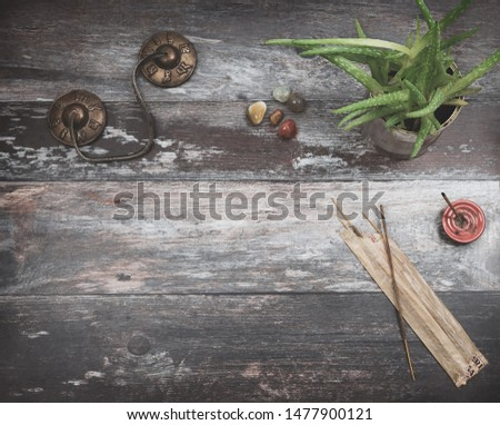 Rustic wooden table with plant, incense sticks, small stones and Tibetan meditation prayer bells with the spiritual the spiritual words Om mani padme hum, translated as The jewel is  is in the lotus