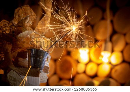 Rustic wooden wall with a sparkler and golden bokeh Christmas concept #1268885365