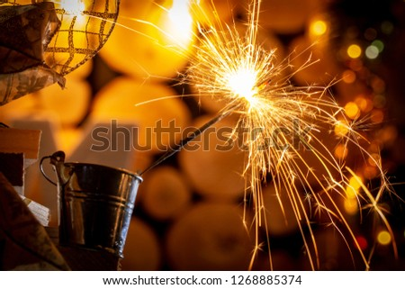 Rustic wooden wall with a sparkler and golden bokeh Christmas concept #1268885374