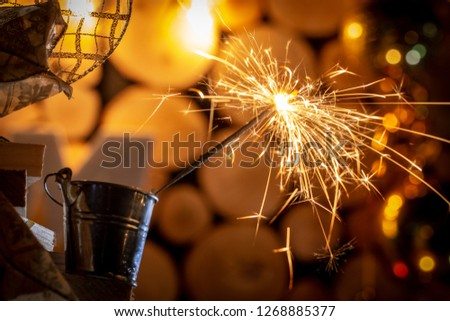 Rustic wooden wall with a sparkler and golden bokeh Christmas concept #1268885377