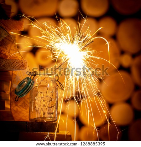 Rustic wooden wall with a sparkler and golden bokeh Christmas concept #1268885395