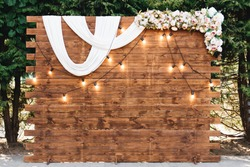 Rustic wooden wedding arch with retro garland decorated with flowers for wedding ceremony newlyweds