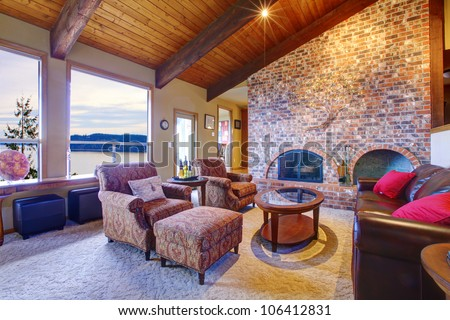 Rustin living room with wood ceiling with brick fireplace.