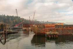 Rusting cargo barge with background cranes.