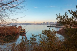 Rusting cargo barge with distant Seattle skyline background.