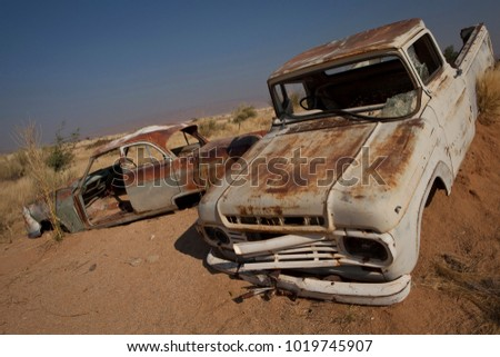 Rusting cars submerged in sand #1019745907