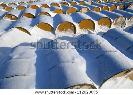 Rusting discarded oil barrels, oil drums in the arctic snow, Canada