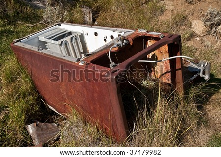 Rusty, abandoned refrigerator lying in a grassy area in a Montana ghost town