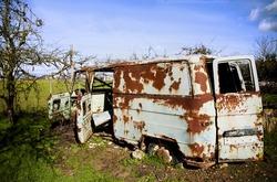Rusty abandoned van in green field.