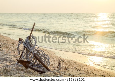 RUSTY ANCHOR WET BEACH SAND AND WHITE SEA-WAVE FOAM
