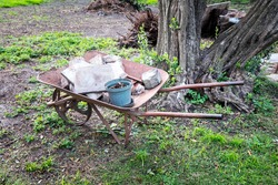 Rusty and broken wheelbarrow in an abandoned garden. Concept of desolate, heavy, poverty, agriculture and nature left behind.