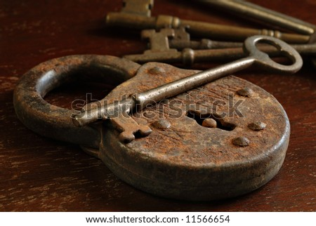 Rusty antique padlock with skeleton keys on a vintage wooden table. Macro still-life with side lighting to emphasize texture.  Shallow dof.