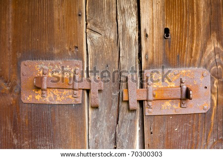 Rusty bar locks on wooden door of historic half-timbered house.