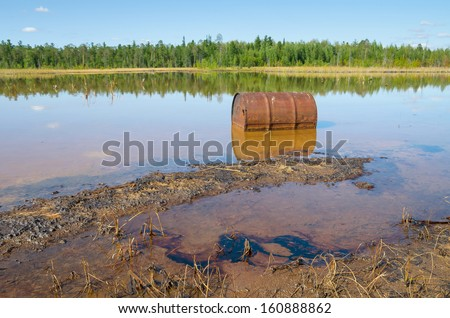 Rusty barrel and traces of the poured oil in the lake