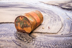 Rusty barrel oil on a partly black coloured beach illustrates the pollution of environment by oil spills