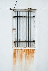 Rusty bars covering an unused window