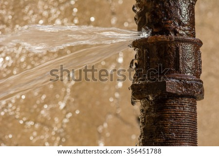 Rusty burst pipe spraying water after freezing in winter.