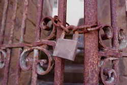 Rusty carved gate and chain with a lock closes the stairs to an abandoned house