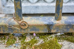Rusty cast iron rod over old weathered concrete surface covered with sand and green moss