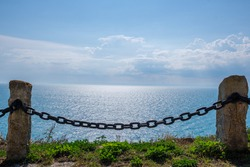 Rusty Chain Barrier With Beautiful Sky and Sea Water In The Background To Prevent People Fall From The Cliff