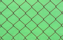 Rusty chain link fence on green blur background, shallow focus