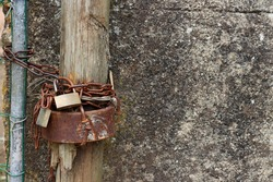 Rusty chains are wrapped around an old wooden post. Rusty chains, rusty nails and padlocks.
