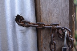 rusty chains hold the door closed. old rotted chain and padlock on the carriage. Rust lock and chain on fence for house protection. Old and rusty chain texture