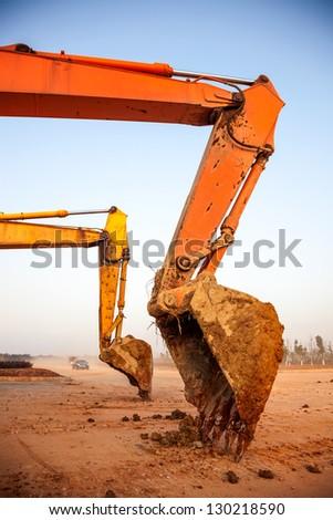 rusty claw of a bulldozer under blue sky