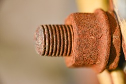 Rusty connecting bolt with nut, old abandoned metal element.