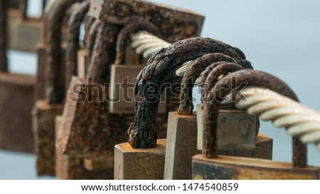 Rusty, corroded love locks / padlocks attached to a bridge. Close up with shallow depth of field #1474540859