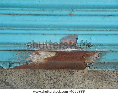 rusty, corroded metal roll-up door once painted sky blue provides a textured background