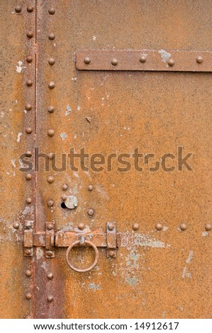 Rusty, corroded old metal door with latch, ring and bolts