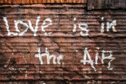 rusty corrugated iron door with a written message of love is in the air