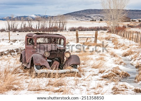 Rusty, dilapidated, abandoned vehicle in a field in rural America on a winter day