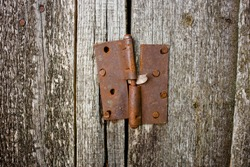 Rusty door hinge on the wooden boards of the old barn, front view close-up