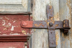 rusty door hinges close-up on an old wooden door.  Forged metal products made in the last century.