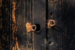 Rusty eye bolts attached to a burned wooden door lit by the evening sun