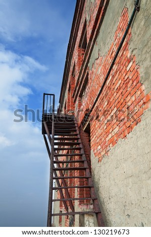 Rusty fire escape on the wall of the destroyed building