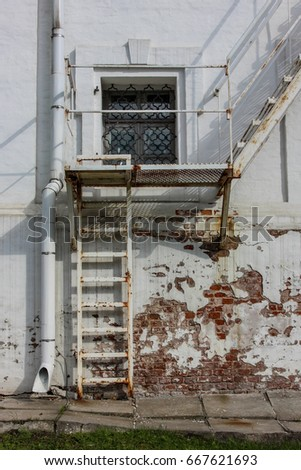 Rusty Fire Stairs Outside An Old White Building