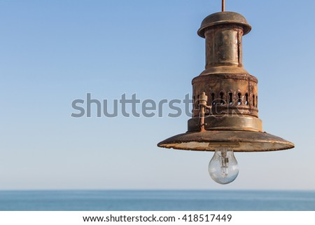 Shutterstock Rusty fishing lamp on a blue sky with sea