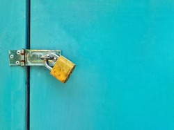 rusty golden lock with locked blue metal door texture background with space