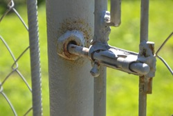 Rusty gray bar on gate on green grass background
