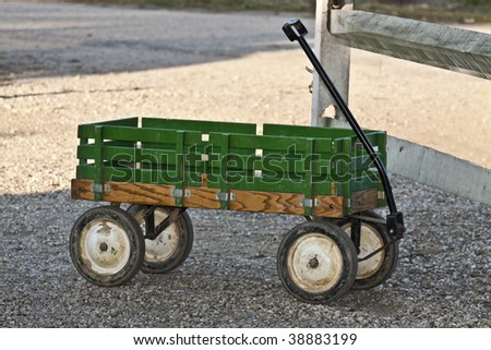 Rusty Green Wagon Parked by a Wood Fence