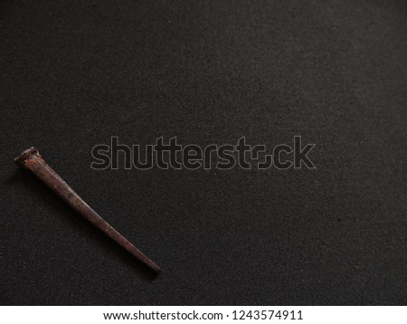 Rusty handmade square cut nails on charcoal grey background  #1243574911