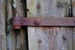 Rusty hinge on a wooden door