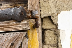 Rusty hinge with wooden door at old house