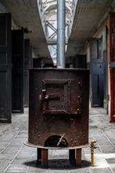 Rusty iron stove in corridor of former old prison with open doors